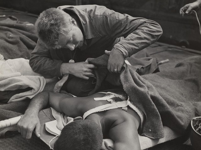 Victor Jorgensen (American, 1914-1994), Untitled (Corpsman checks wounds) from 1945.