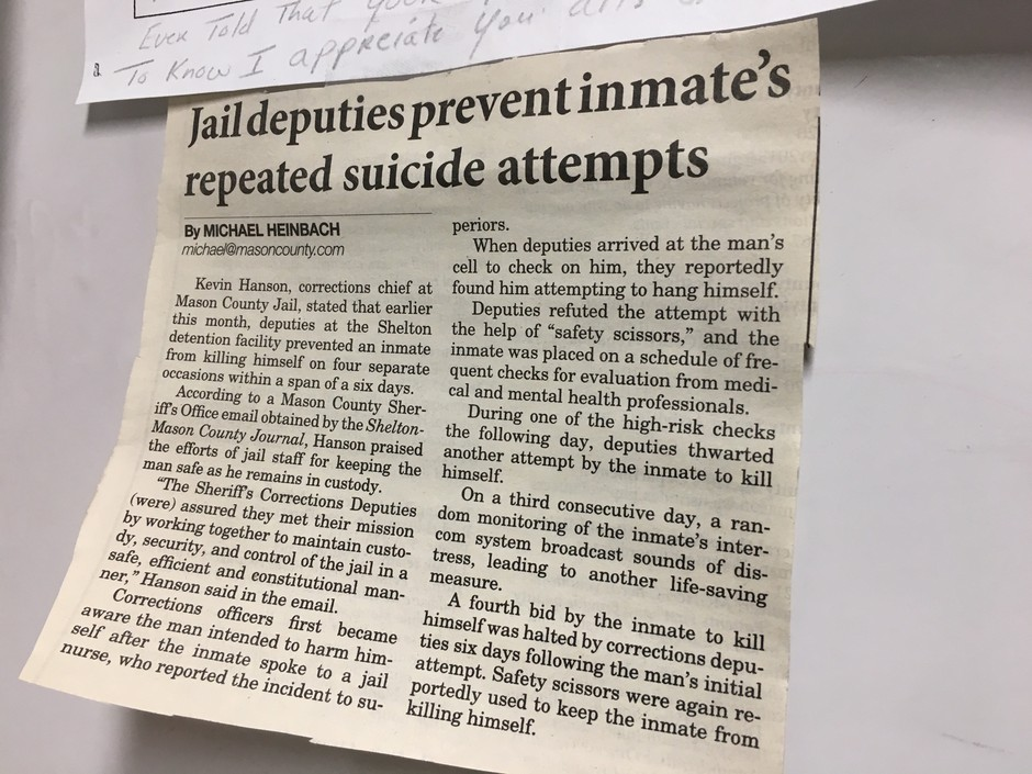 A newspaper article hanging in the Mason County Jail office talks about suicide attempts in the jail.