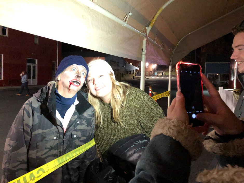 People snap pictures with zombie Monica Burleson. She drags a foot around the streets of Haunted Palouse and tries to get scares and starts as patrons wait to get in line for the haunted houses and hayride.