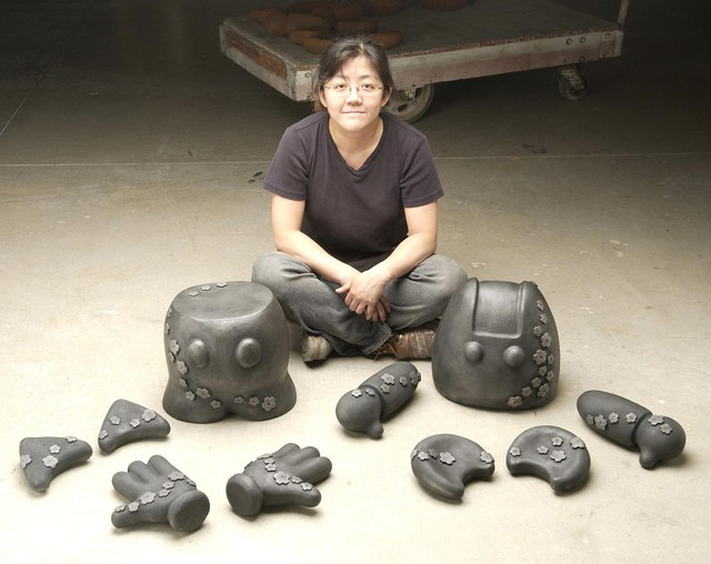 Junko Iijima sits next to her cast iron art pieces. If you look closely, you'll notice the pieces are from easily identifiable icons of pop culture like Mickey Mouse and Hello Kitty.