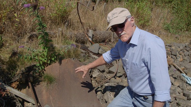 Paul Fishman points out one of the rusty World War II ship scraps still left on the bank of Portland's Willamette River.