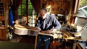 Master luthier Jeffrey Elliott sands down the neck of one of the many custom guitars he makes for musicians around the world.