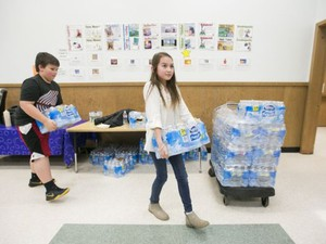 Fourth graders Emi Vu Magee and Brian Emmrich carry packages of bottled water back to their classroom at Valley Inquiry Charter School in Salem on Wednesday, March 16, 2016. Students and staff at the school have been drinking bottled water since March 2015, after high levels of copper were found in their water supply. The school previously had problems with lead levels in 2011 and 2014, but after replacing pipes and fixtures they tested within regulatory limits twice in 2015.