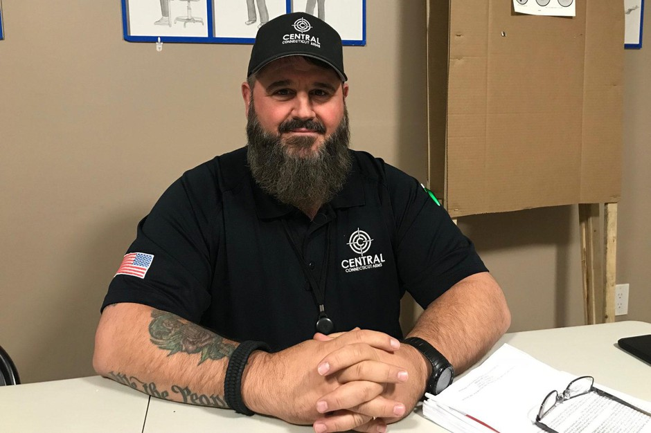 Rob Pizzi sits in the training room of his gun shop, Central Connecticut Arms. He's never sold bump stocks.