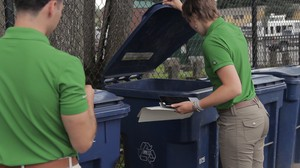 Interns Audrey Taber and Crhistian Cuellar examine the contents of the recycling bins at Parkview Apartments in Auburn, Washington to find potential topics for conversation with residents.