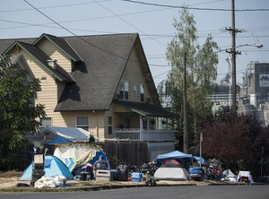 Tents and belongings line the street edge outside Share House, the men's homeless shelter on the west edge of downtown Vancouver.