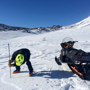 A snow-machine rider takes a snowpack reading as part of Community Snow Observations, a NASA-sponsored citizen science project.