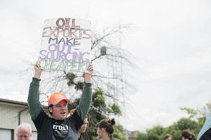 A protester hoists a sign at a 2016 protest against oil trains in Vancouver, Washington.
