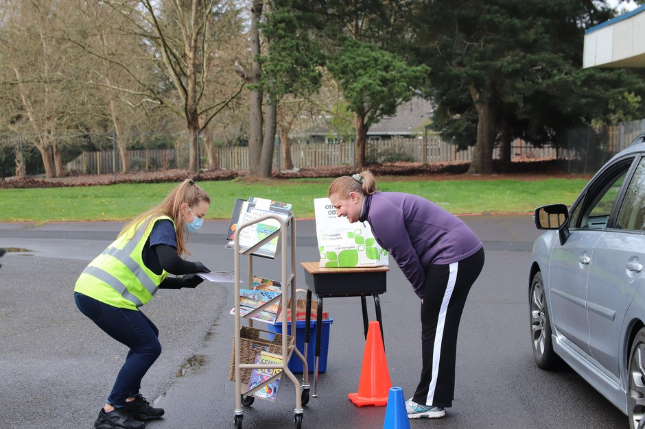 Third grade teacher Jessica Neal helps a parent choose a few books to bring home. Along with laptops, the staff at Rock Creek Elementary in Beaverton provided supplies to help their students continue their lessons while staying at home.