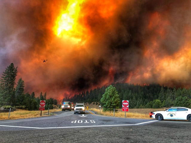 Two red fire trucks, a white truck, and a white Highway Patrol car stopped at a freeway exit ramp. Flames burn on a hillside in the distance and a red helicopter flies above.