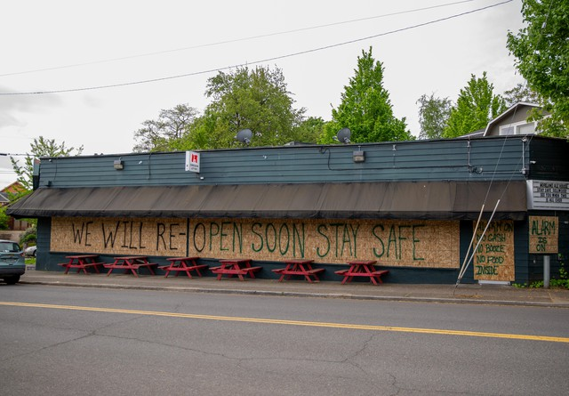 Sheets of plywood adorned with messages about the alarm being on and plans to reopen soon cover the doors and windows of the Moreland Ale House in Portland, Ore., on Wednesday, April 29, 2020.