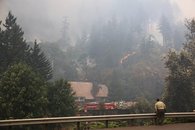An officer looks on as fire crews work on the Eagle Creek Fire.
