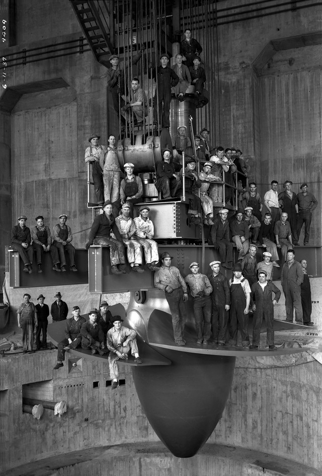 Workers on giant turbine being lowered into Bonneville Dam (1937).