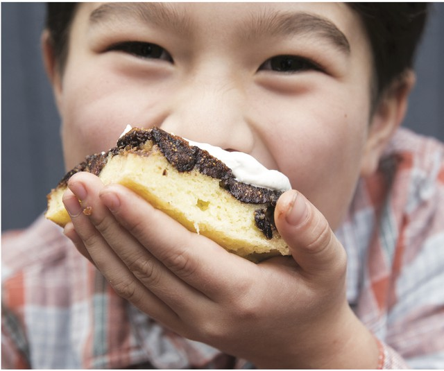"""Rachel Yang's older son, Pike Chirchi, 7, takes a bite of Upside-Down Fig Mochi Cake with Bleu Cheese Whip. The sweet-savory """"dessertish"""" rice cake can be made with dried apricots instead of Mission figs."""