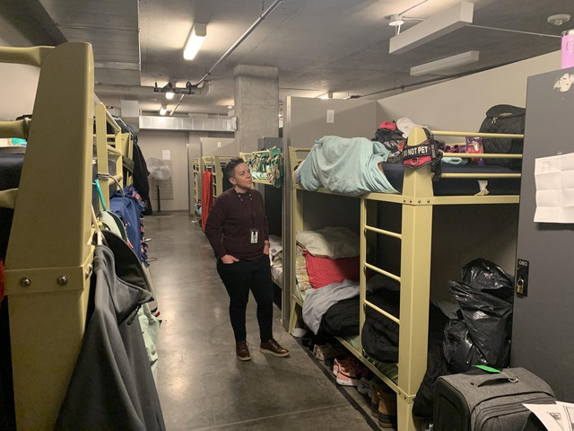 Stacy Borke, the senior director of programs for Transition Projects Inc., looks at the beds in Doreen's Place, a shelter in downtown Portland. The county has asked shelters to try and create a six foot buffer around the beds of sick guests.