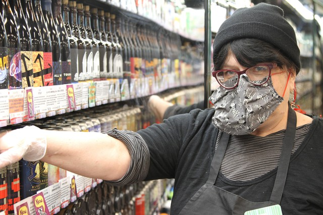 """Patty Beavers wears protective gear at Green Zebragrocery in southeast Portland,""""I'm just grateful that I'm able to work right now. … Just hang in there, be clean, be safe, this will pass. It always has and it will."""""""