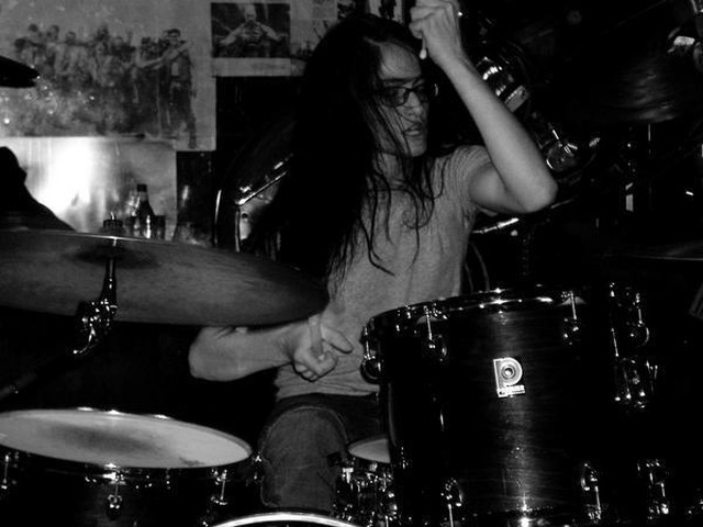 Lauren K. Newman doing what she does best, thrashing on the drums.