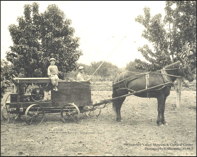 A Wenatchee Sprayer made by A. D. Browning, Wenatchee. Two men, one with bamboo spray pole, and one small boy sitting on top of sprayer pulled by one horse in a fruit orchard in Wenatchee. Because farmers did not know of the potential toxicity or longevity of pesticides in use at the time, Washington law exempts farmers from being liable for contamination from legally applied pesticides.