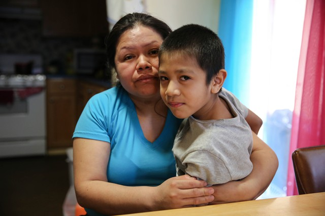 Rosalina Guzman sits with her youngest son. She and her husband, Roman, have five children who were born in the United States and are citizens.