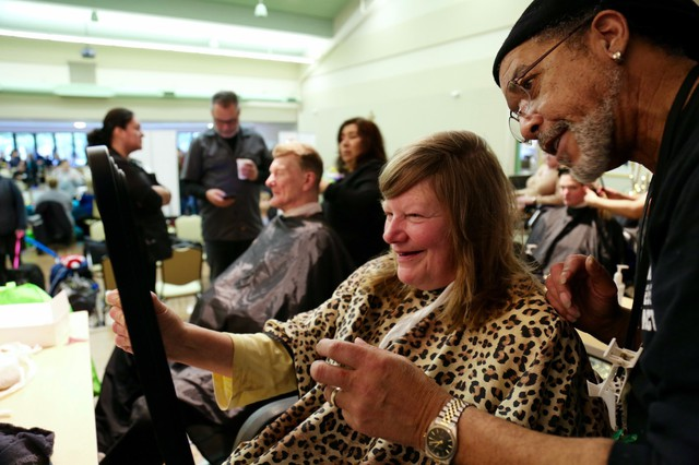 Retired stylist Derek Thompson, right, holds up a mirror to show Debbie her new haircut. Thompson's organization Hands of Favor provides free hair cuts and styling to the homeless.