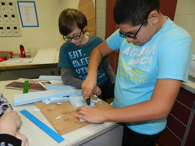Seventh graders Michael Herrera and Nicolas Barbee cut foam for the model boat's hull.
