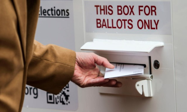 A ballot is turned in at an official county ballot return box in Oregon.