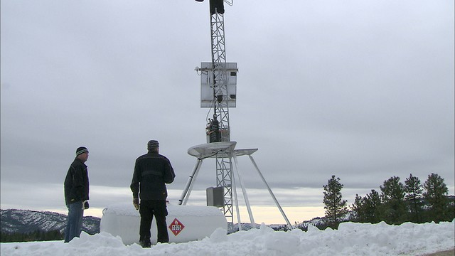 Derek Blestrud and Brandel Glenn with Idaho Power are looking at the cloud seeding tower located near Idaho City.