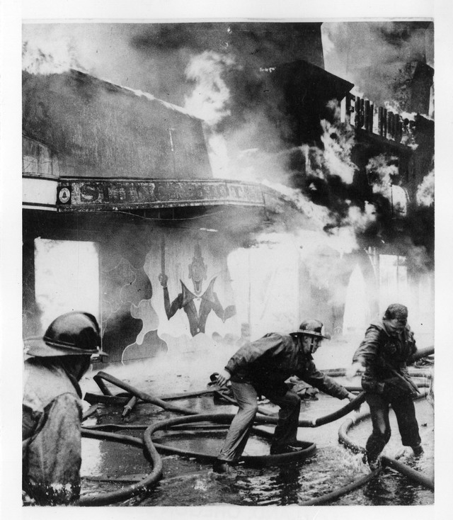 """Jantzen Beach Amusement Park fire. Firemen try to move hoses out of the way of building about to collapse,"" March, 1960."