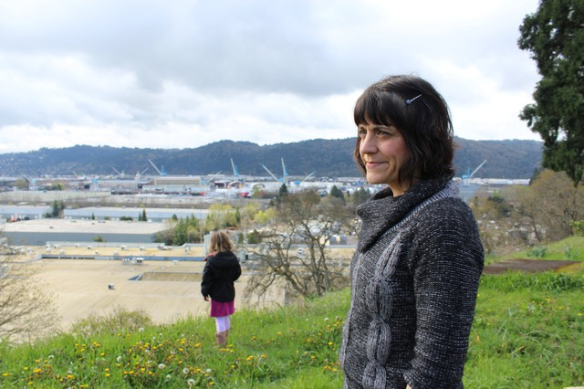 North Portland resident Stacey Schroeder stands on the bluff along WIllamette Boulevard overlooking Swan Island and the Daimler Trucks North America plant, as her daughter picks dandelions in the distance. Schroeder and other neighbors blame Daimler for paint odors in their neighborhood, and they blame the Oregon Department of Environmental Quality for failing to fix it.