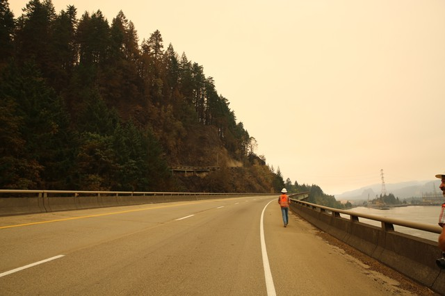 A worker walks along a closed Interstate 84 on Thursday, Sept. 14, 2017. The highway will remain closed until authorities deem it safe to re-open with the ongoing Eagle Creek Fire.