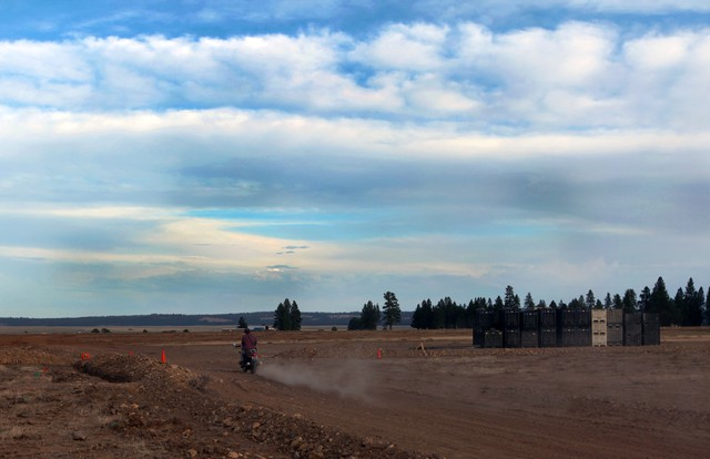 A worker drives off in the direction of the main event area and the Big Summit Prairie.