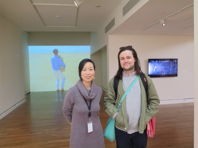 "Grace Kook-Anderson, PAM's Curator of Northwest Art, stands with artist Sam Hamilton in the middle of his exhibition, ""Standard Candles."""