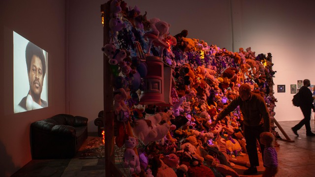 """Abigail DeVille's complex installations marry elements like this cluster of found toys. Around the corner, visitors take in a viewing of """"Arresting Power: Resisting Police Violence in Portland, Oregon"""" by Jody Darby, Julie Perrini, and Erin Yanke."""