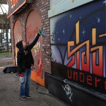 """Bree Judah,paint location foreman for Grimm, defaces the sign she and a coworker painted a day earlier to blend it into the other wall graffiti. """"You can't get attached to it,"""" she says."""
