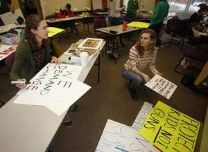 Vancouver School of Arts and Academics students Greta DuBois, left, and Aubree Radtke make signs at the Evergreen Education Association offices for the March for Our Lives, scheduled for Saturday. They're among a group of student organizers leading the upcoming demonstration.