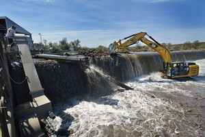 An excavator breaks a logjam in April 2013 above the Three Mile Dam on the Umatilla River north of Hermiston. The Oregon Water Resources Department is considering seeking tougher dam inspection laws.