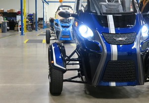 A row of Acrimoto's distinctive three-wheeled electric vehicles sit in its Eugene, Ore. factory.