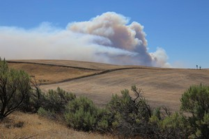 Smoke from the Substation Fire rises over the hills near Moro, Oregon, Wednesday, July 18, 2018.