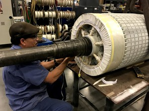 In H&N Electric's shop, Jose Gutierrez finishes up one of the last steps of repairing a part of a wind turbine generator.