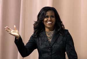 "Former first lady Michelle Obama waves to the audience during a stop on her book tour for ""Becoming,"" in Washington, Sunday, Nov. 25, 2018."