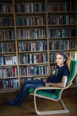 Garber at his home in front of his bookshelf. He owns an estimated 1,500 books.
