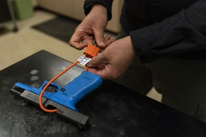 Sgt. Brandon White of the Multnomah County Sheriff's Office puts a cable lock on a training Glock on Jan. 14, 2019 in Portland, Oregon. The sheriff's office gives out gun locks for free to anyone who wants one.
