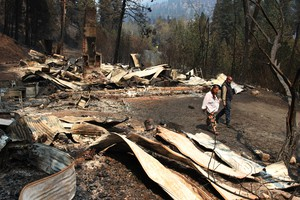 Tina Couey walks through the remains of her mother's home and property after the Canyon Creek Complex fire moved through the area in 2015.