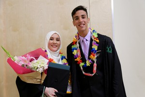Graduating seniors Salma Bashir and Ahmed Al-Dulaimi pose for photographs after receiving their diplomas.