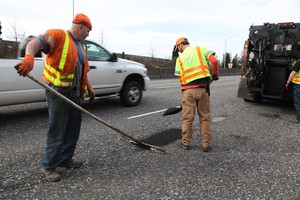 An Oregon Department of Transportation crew fills potholes on Highway 26 in this April 14, 2017, file photo.