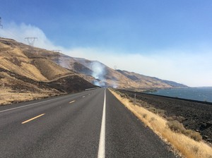 A fire burns along the Columbia River south of Highway 14 in Washington state Wednesday afternoon.