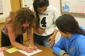 Kris Mulvihill (left) works with high school students at Riverside High School in Boardman. Mulvihill directs the K-12 portion of the Eastern Promise program.