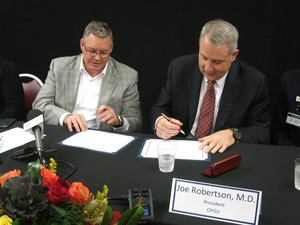 OHSU President Joe Robertson and Adventist's chief Bill Wing sign a deal to affiliate.