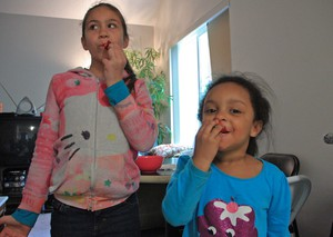 Adrianna and Naniloa Bannister enjoy fresh strawberries.