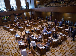 Democratic members of the Oregon Senate stand in the mostly empty Senate chambers at the Oregon Capitol in Salem, Ore., on Thursday, June 27, 2019. On the eighth day of a walkout by Republican senators, Oregon Senate President Peter Courtney adjourned the session shortly after it began due lacking the required number of senators to meet a quorum.